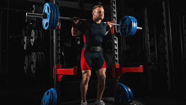 MAn squatting with lifting belt