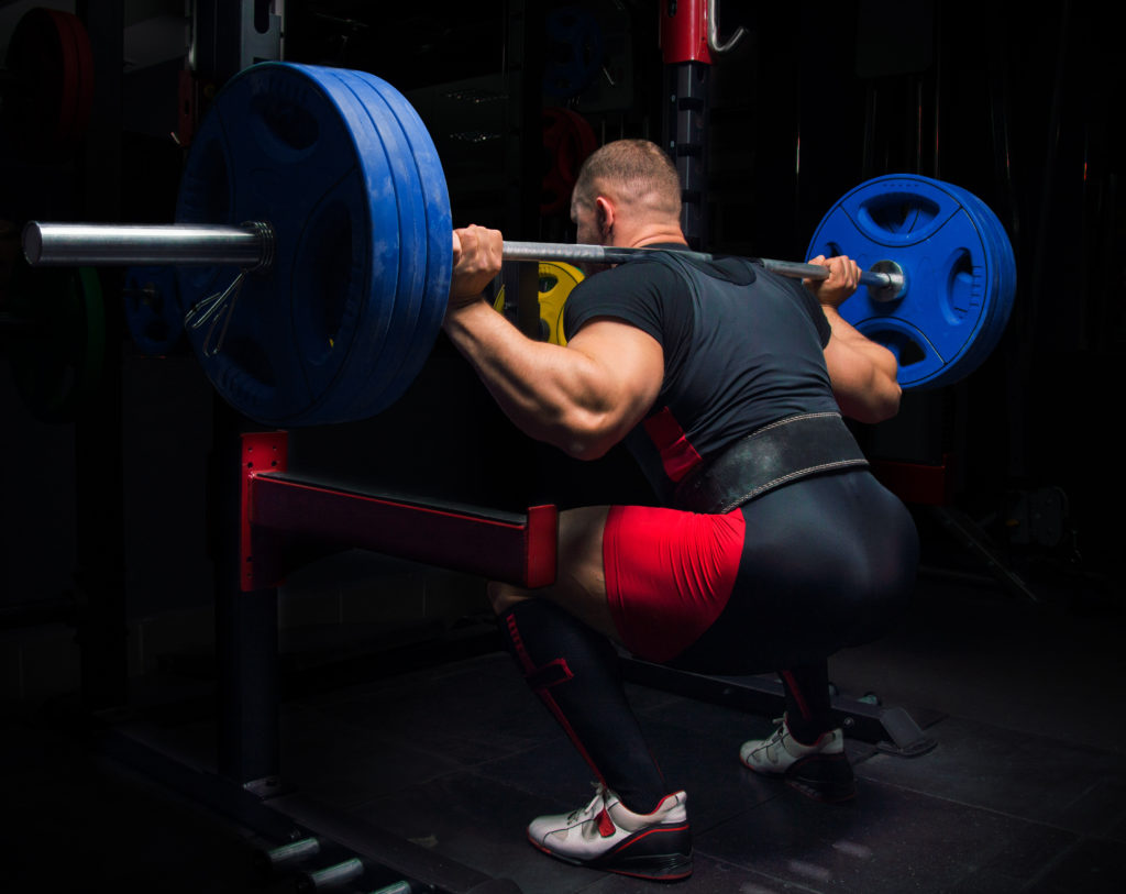 Powerlifter performing a squat while using a weight belt