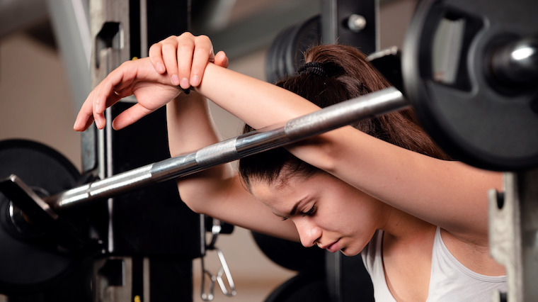 Women leaning on racked barbell.