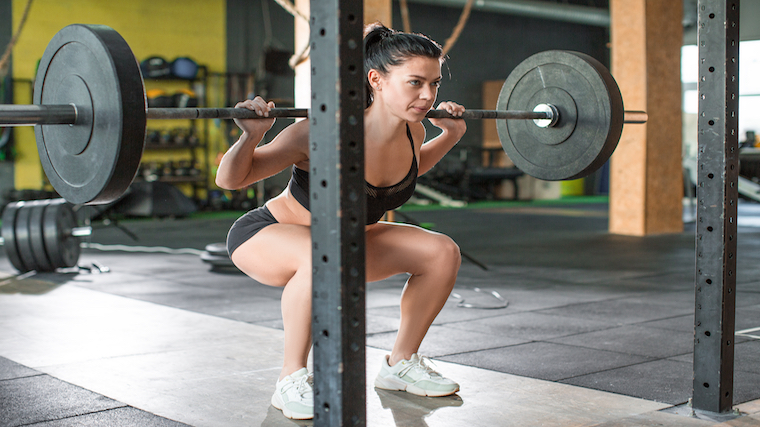 Women performing loaded barbell back squat in front of rack.
