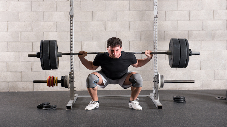 Man squatting with barbell in front of squat rack.