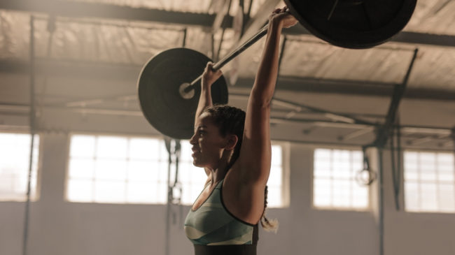 woman pressing barbell overhead