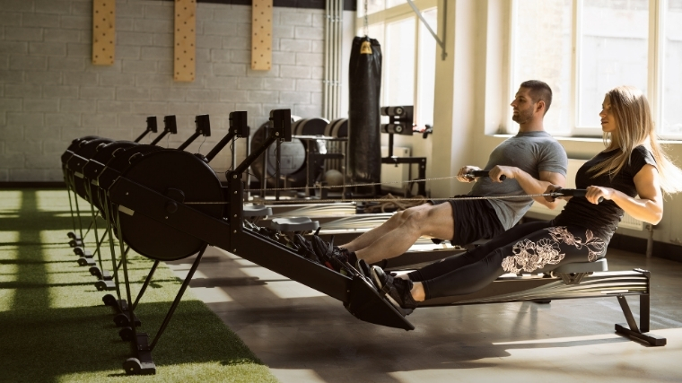 Man and woman rowing on erg