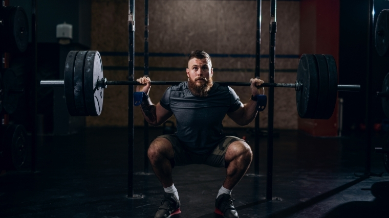 Man squatting with barbell on back