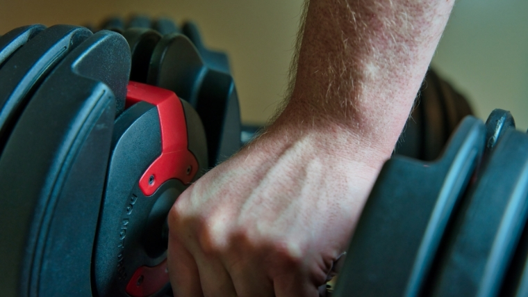 Man holding adjustable dumbbell