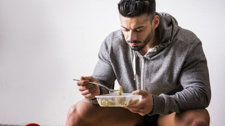 Athlete eating out of tupperware
