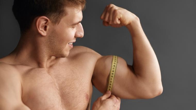Man measuring biceps muscle