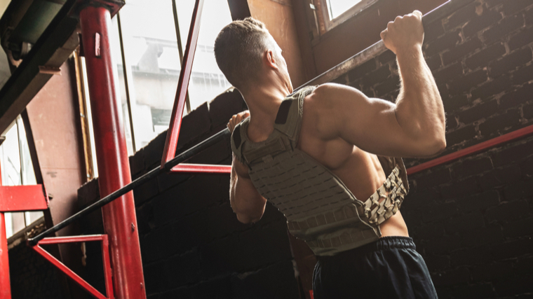 man doing pull-up with weight vest