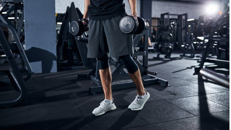 man standing with dumbbells